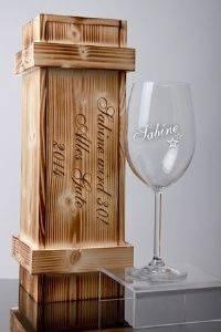 Ein graviertes Weinglas in einer schicken Holzkiste
